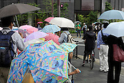 little school children walking with bright colored umbrellas Japan