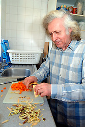 Resident at a homeless hostel prepares vegetables for the evening meal; Liverpool, The hostel is funded through the Supporting People government scheme to help vulnerable people improve their lives,  The hostel helps men overcome drink; drug and mental health problems,