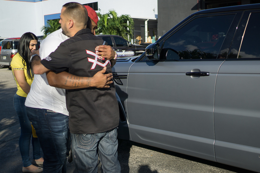 DORAL, FLORIDA, DECEMBER 11, 2015<br /> Alex Vega, right, owner of The Auto Firm, a South Florida car customizing and restoring shop which has a vast clientele of professional athletes and entertainers, gets a hug after giving a car back to client Pablo Sandoval and wife Yulimar Martins in his office. Sandoval was picking up his customized Range Rover.<br /> (Photo by Angel Valentin/Freelance)