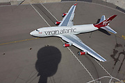 Aerial view (from control tower) of Virgin Atlantic airliner's wing and engine at London Heathrow airport. Taxiing along the centreline that helps pilots navigate to specific locations around the airport consisting of five terminals on a site that covers 12.14 square kilometres (4.69 sq mi). London Heathrow is a major international airport, the busiest airport in the United Kingdom and the busiest airport in Europe by passenger traffic. It is also the third busiest airport in the world by total passenger traffic, handling more international passengers than any other airport around the globe. <br /> From the chapter entitled 'Up in the Air' and from the book 'Risk Wise: Nine Everyday Adventures' by Polly Morland (Allianz, The School of Life, Profile Books, 2015).