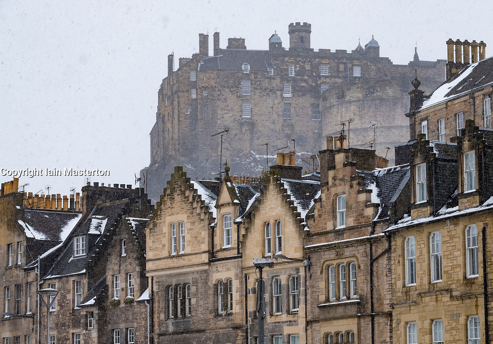 View of Edinburgh Castle and historic old houses from the Grassmarket during heavy snow fall in Edinburgh , Scotland, United Kingdom