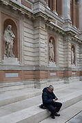 A man uses his mobile phone beneath the figures of Gottfried Leibniz, Georges Cuvier and Carl Linnaeus at the rear of the Royal Academy in Burlington Gardens, on 30th April 2019, in London, England