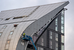 © Licensed to London News Pictures. 25/05/2021. London, UK. A building maintenance worker leans out of a window as another on a crane inspects a large section of cladding that came loose at the Arc Tower in Ealing. Emergency services were forced to close a section of Uxbridge Road while the building was made safe. Photo credit: Peter Manning/LNP