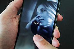 Using an iPhone 6 Plus smart phone to book taxi using Uber online app