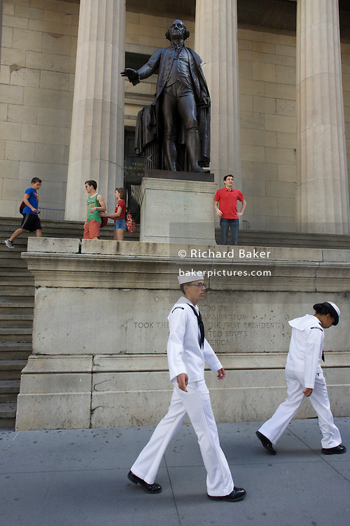 Two US Navy sailors walk past the statue of first President George Washington outside the Federal Hall National Memorial on Wall Street, New York City.
