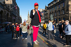 Edinburgh, Scotland, UK. 15 August 2019. Warm sunny weather in Edinburgh brought thousands of tourists onto the Royal Mile to enjoy the many street performers and actors promoting their shows during the Edinburgh Festival Fringe. Donald Trump makes an appearance promoting show Trump's Fake TV.  Iain Masterton/Alamy Live News ++ Editorial Use Only ++