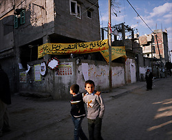 Children are seen outside a home, decorated with martyr posters and signs decrying civilian deaths from Israeli artillery fire, Beit Hanoun, Gaza Strip, Palestinian Territories, Nov. 24, 2006. According to Human Rights Watch, since September 2005, Israel has fired about 15,000 rounds at Gaza while Palestinian militants have fired around 1,700 back.