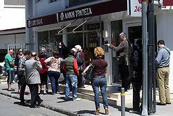 People wait outside a branch of Laiki Bank before the reopening of the bank in Nicosia, capital of Cyprus, on March 28, 2013. Surprisingly few lined up outside banks in Cyprus when they reopened for business at noon on Thursday -- to the relief of authorities which have feared a run on the banks following a closure since March 16. Strict limits on bank transactions have been announced by the Central Bank and the ministry of finance in a bid to prevent a massive outflow of cash. A Central Bank official said banks would be open for transactions between 12:00 noon and 18:00 local time (10:00 GMT and 16:00 GMT), instead of the normal 08:30 to 13:00 local time bank hours. The decree imposing controls on bank transaction limits cash withdrawal to 300 euros per day per bank account and entirely prohibits payment by check. However, credit card holders can use them for commercial transactions for unlimited amounts of money., Nicosia, Cyprus, March 28, 2013. Photo by Imago / i-Images...UK ONLY.