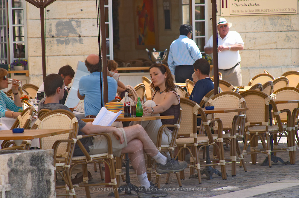 A square in Saint Emilion with Cafes with outside seating terrasse with parasols, people drinking and eating in the sun. Many tourists Saint Emilion Village Bordeaux Gironde Aquitaine France