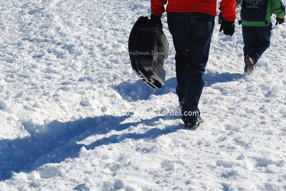 Boy of 7 carries his sledge back up the snow covered mountain slope