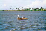 Mozambikanen steken een lagoon over in op een houten vlot