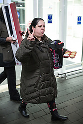 © Licensed to London News Pictures . 27/11/2015 . Salford , UK .A woman eating a mince pie , leaving a branch of Tesco in Pendleton , Salford , this morning (Friday 27th November) as people behind queue for Black Friday offers . Last year (2014) scuffles and fights were reported amongst queuing bargain-hunters . Photo credit: Joel Goodman/LNP