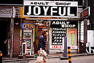 A woman passes and adult shop in Tokyo, Japan.