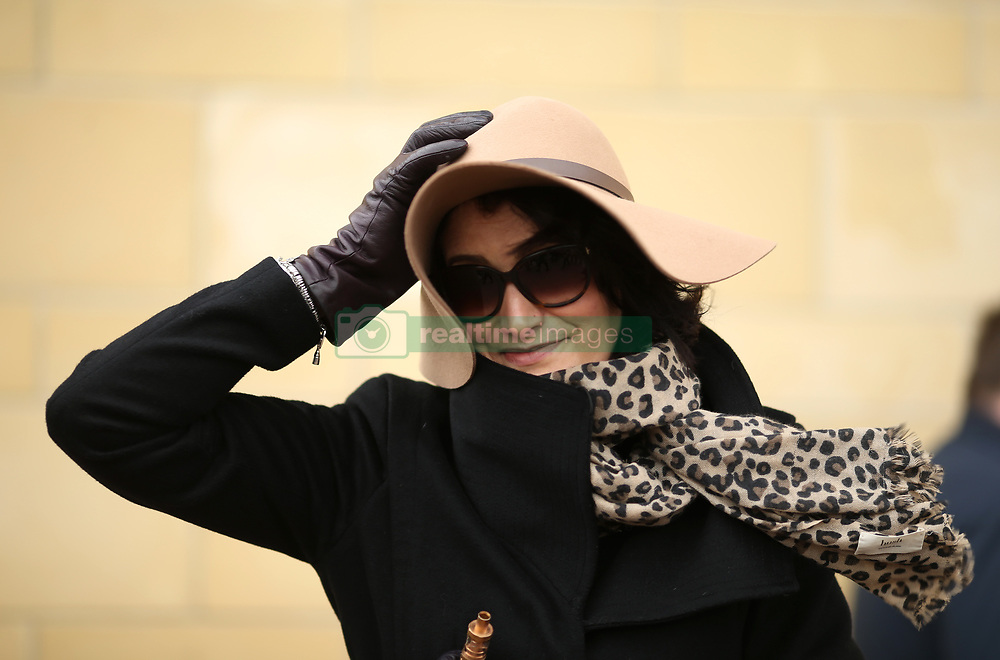 A female racegoer holds onto her hat during Ladies Day of the 2018 Cheltenham Festival at Cheltenham Racecourse. PRESS ASSOCIATION Photo. Picture date: Wednesday March 14, 2018. See PA story RACING Cheltenham. Photo credit should read: Steven Paston/PA Wire. RESTRICTIONS: Editorial Use only, commercial use is subject to prior permission from The Jockey Club/Cheltenham Racecourse.