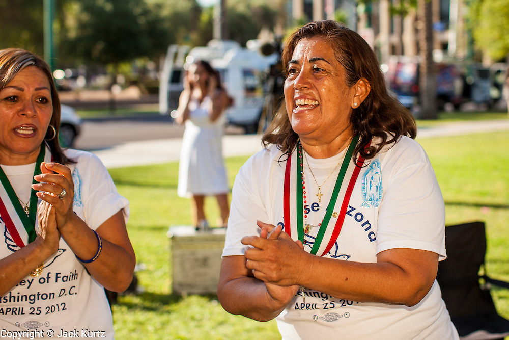 25 JUNE 2012 - PHOENIX, AZ: ROSA MARIA SOTO prays and celebrates at the Arizona State Capitol in Phoenix, AZ, Monday after the US Supreme Court struck down most of SB1070. The lawsuit, US v. Arizona, determines whether or not Arizona's tough anti-immigration law, popularly known as SB1070 is constitutional. Among other things, the law requires police officers to check the immigration status of anyone whom they arrest, allows police to stop and arrest anyone whom they believe to be an illegal immigrant, makes it a crime for someone to be in the state without valid immigration papers, and makes it a crime to apply for or hold a job in Arizona without proper papers. The federal government sued Arizona because it believes the law is invalid because it is trumped by federal immigration laws. The court struck down most of the law but left one section standing, the section authorizing local police agencies to check the immigration status of people they come into contact with.    PHOTO BY JACK KURTZ