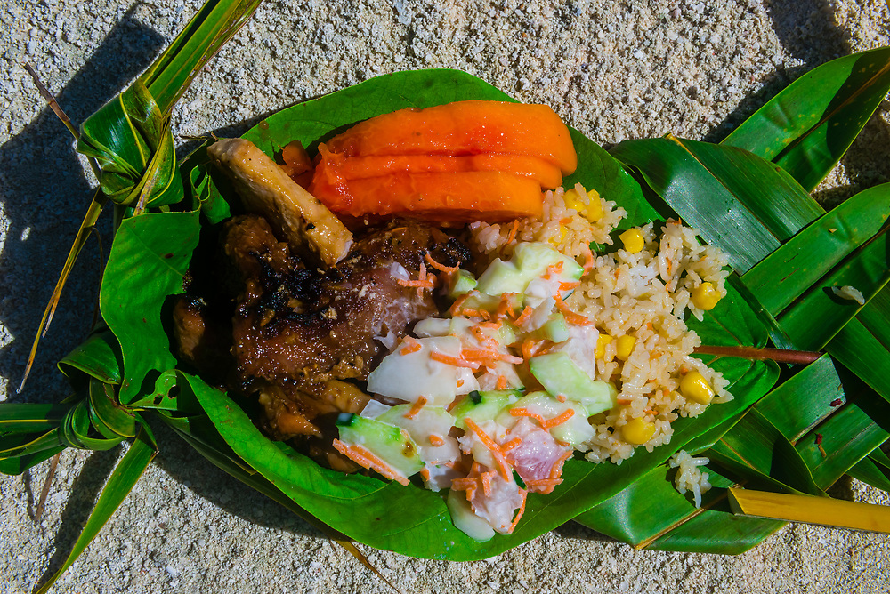 Polynesian lunch served on a plate made from palm leaves, Haapiti Motu (a small private island) off Bora Bora, Society Islands, French Polynesia.