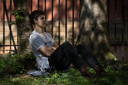 © Licensed to London News Pictures . 21/04/2015 . Manchester , UK . A man sits below a tree in the sunshine in Manchester's Sackville Park , this afternoon (Tuesday 21st April 2015) . Photo credit : Joel Goodman/LNP