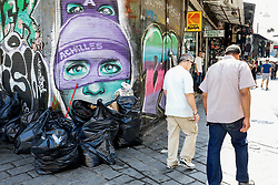 June 27, 2017 - Athens, Greece - Men walk next  a pile of garbage in the center of Athens. Municipality workers have been on strike for almost a week, hindering trash collection across the country. (Credit Image: © Eurokinissi via ZUMA Wire)