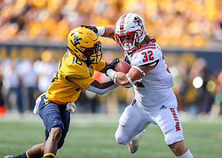 Sep 14, 2019; Morgantown, WV, USA; North Carolina State Wolfpack linebacker Drake Thomas (32) intercepts a pass and is then tackled by West Virginia Mountaineers wide receiver Winston Wright (16) during the third quarter against the West Virginia Mountaineers at Mountaineer Field at Milan Puskar Stadium. Mandatory Credit: Ben Queen-USA TODAY Sports