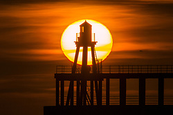 April 26, 2018 - Whitby, Yorkshire, UK - Whitby UK. Picture shows the sun rising this morning behind the lighthouse at the end of Whitby pier on the Yorkshire coast. (Credit Image: © Andrew Mccaren/London News Pictures via ZUMA Wire)