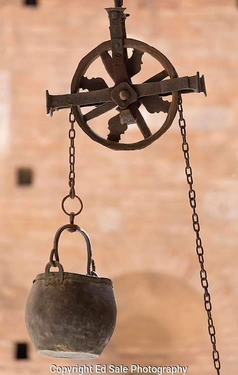 A old water well bucket and pulley system hang in a courtyard in Sienna, Tuscany, Italy.