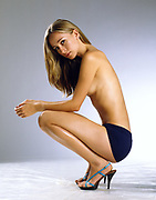 Topless woman squatting on white background with arms on knees