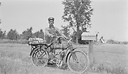 8706-24.  A Postal mail carrier is working a rural free delivery route near Newell, S.D. His motorcycle is a Wagner 4-11. His hat identifies his route as RFD3.