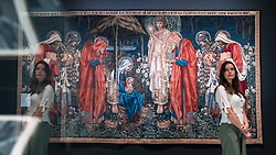 """© Licensed to London News Pictures. 22/10/2018. LONDON, UK. A staff member stands next to """"The Adoration of the Magi"""", 1894, by Edward Burne-Jones.  Preview of the largest Edward Burne-Jones retrospective to be held in a generation at Tate Britain.  Burne-Jones was a pioneer of the symbolist movement and the only Pre-Raphaelite to achieve world-wide recognition in his lifetime.  The exhibition runs 24 October to 24 February 2019.  Photo credit: Stephen Chung/LNP"""