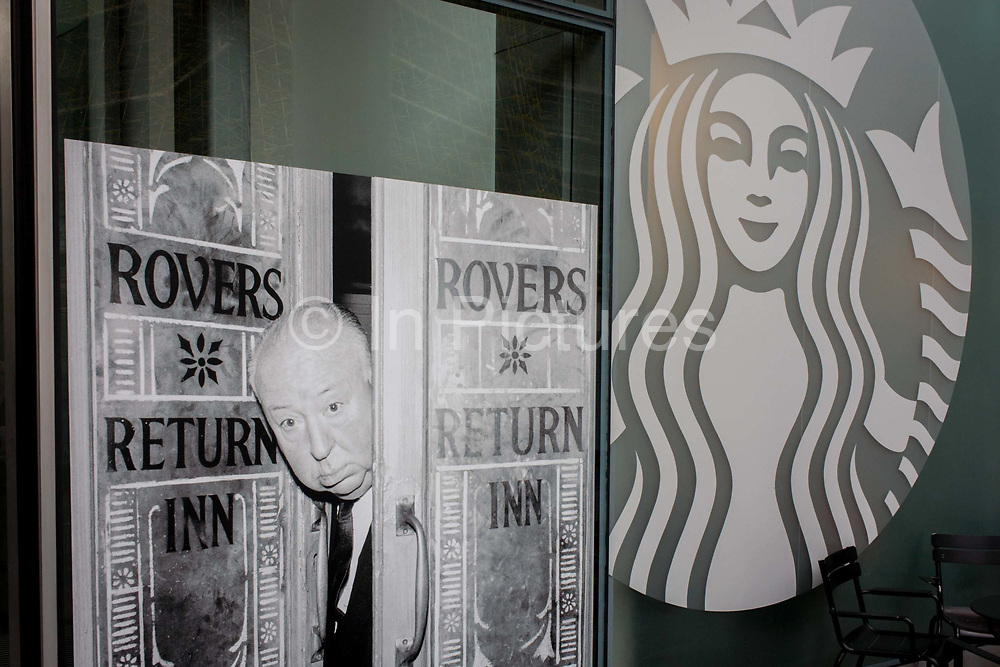 Photograph of film director Alfred Hitchcock on the Coronation Street TV soap set alongside the modern Starbucks logo. The image is located outside the London offices of IPC Media who publish magazines such as TV Times, a television listings publication celebrating its 60th anniversary. The faces and portraits of celebrities known to the world of film and TV are being exhibited on the street outside and include this publicity picture from the 60s when Hitchcock must have visited the set of longest-running soap Coronation Street about working class folk in northern England, centred around its pub The Rovers return. Alfred Hitchcock (1899-1980) peers through the doors of the pub in June 1964, taken by Joe Darby for the Daily Herald.