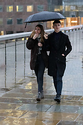 © Licensed to London News Pictures. 01/12/2018. London, UK.  A coupole walking with an umbrella during rain and wet weather, near London Bridge on the first day of meteorological winter.  Photo credit: Vickie Flores/LNP