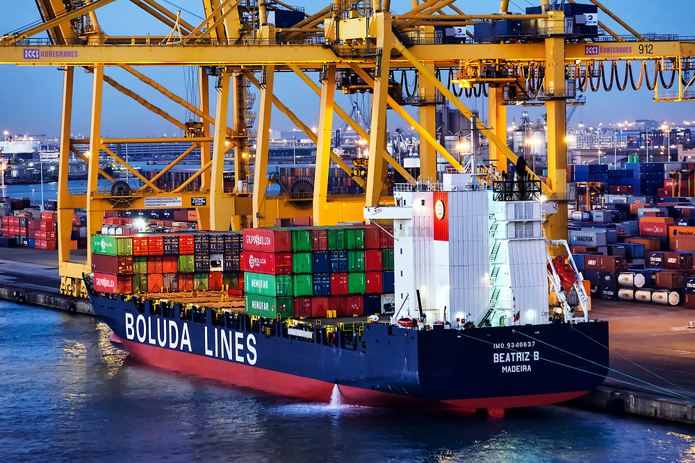 Cargo containers being loaded on to a shipping freighter , Barcelona, Spain