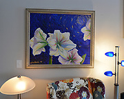 The living room features a group of paintings of flowers by Madison, Wisconsin artist Yukari. In her short career (1996-1998) as an artist, Yukari only created ten acrylic paintings, and Sheridan and Rikki Glen own four of those ten. Sheridan and Rikki Glen are At Home in their Tanglewood subdivision home in Caseyville, IL on Wednesday January 16, 2019. <br /> Photo by Tim Vizer