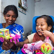 CAPTION: Home-Based Educator (HBE) Sakamma has been able to help eight-year-old Sangeetha, who has cerebral palsy, improve her fine motor skills by playing with various teaching and learning materials. Sangeetha has also learned to recognise regular visitors to her home, and to say simple words like amma ('mother'). Over the lifetime of the Chamkol programme, Sakamma says we can expect Sangeetha to start walking, and also to learn to write a little and turn those single words into full sentences. LOCATION: Amchawadi (village), Haradanahalli (hobli), Chamrajnagar (district), Karnataka (state), India. INDIVIDUAL(S) PHOTOGRAPHED: Sakamma (left) and Sangeetha (right).