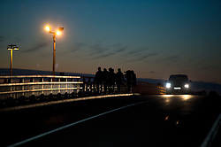 © Licensed to London News Pictures. 09/08/2015. Calais, France. A large group of migrants cross a bridge overlooking the train tacks in the town of Freshen near Calais in Northern France as they head to the train tracks to the Eurotunnel terminal terminal. Hundreds of migrants attempt to illegally access the Eurotunnel complex each night in order to board a train and reach the UK. Photo credit: Ben Cawthra/LNP