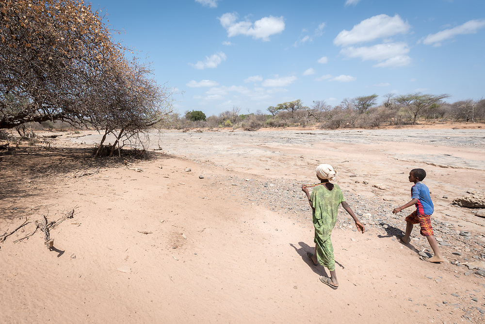 27 January 2019, Burka Dare IDP site, near Micha, Seweyna woreda, Bale Zone, Oromia, Ethiopia: Two Oromo children walk by the dry riverbed near Burka Dare IDP site in Seweyna woreda (administrative unit), Bale Zone, Ethiopia. The Lutheran World Federation supports internally displaced people in several regions of Ethiopia, through emergency response on water, sanitation and hygiene (WASH) as well as long-term development and empowerment projects, to help build resilience and adapt communities' lifestyles to a changing climate.