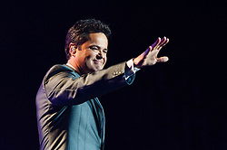 "© Licensed to London News Pictures. 20/01/2013. London, UK.   Donny Osmond of Donny and Marie Osmond performing live at The O2 Arena, on the opening night of their Donny & Marie Live tour Sunday 20 January 2013.  .Donald Clark ""Donny"" Osmond (born December 9, 1957) is an American singer, musician, actor, dancer, radio personality, and former teen idol. Donny Osmond has also been a talk and game show host, record producer and author. In the mid 1960s, he and four of his elder brothers gained fame as The Osmonds on the long running variety program, The Andy Williams Show. Donny went solo in the early 1970s covering such hits as ""Go Away Little Girl"" and ""Puppy Love""...Olive Marie Osmond (born October 13, 1959) is an American singer, actress, doll designer, and a member of the show business family The Osmonds. Although she was never part of her family's singing group, she gained success as a solo country music artist in the 1970s and 1980s. .For over thirty-five years, Donny and Marie have gained fame as Donny & Marie, partly due to the success of their 1976-79 self-titled variety series, which aired on ABC. The duo also did a 1998-2000 talk show and have been headlining in Las Vegas since 2008.   Photo credit : Richard Isaac/LNP"
