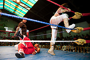 Female wrestler climbing on ropes in ring to jump onto male opponent. Lucha Libre wrestling origniated in Mexico, but is popular in other latin Amercian countries, including in La Paz / El Alto, Bolivia. Male and female fighters participate in the theatrical staged fights to an adoring crowd of locals and foreigners alike.
