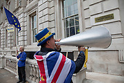 Anti Brexit protester and campaigner Steve Bray wearing European and Union flags uses his loud hailer to comment on proceeding outside the Cabinet Office in Westminster as inside the Tory Cabinet meets to discuss Brexit on 16th August 2019 in London, England, United Kingdom.
