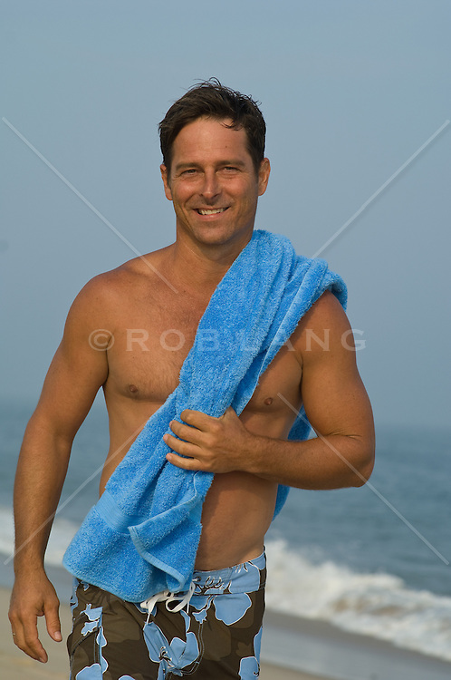 Shirtless man holding a blue towel while enjoying a walk on the beach during sunset in East Hampton, NY