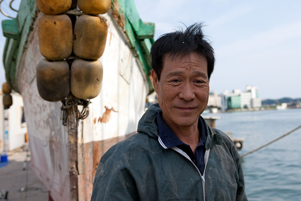 Portrait of the korean worker in front of the fishing boat in Pohang ferry harbor / South Korea, Republic of Korea, KOR, 04 October 2009.