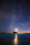 Arched Rock, Milky Way and Moon above surf illuminated by bioluminescent dinoflagellates (a light sensitive plankton that is often present during red tides) at Blind Beach in Northern California's Sonoma Coast State Park.