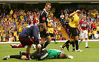 Photo: Frances Leader.<br /> Watford v Burnley. Coca Cola Championship.<br /> 20/08/2005.<br /> <br /> <br /> Burnley's Goal Keeper Brian Jensen lies on the floor injured while Watford's Matthew Spring celebrates the third goal of the game for Watford and referee Matt Messias who allowed play to continue, walks past.