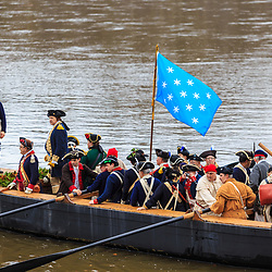 Washington Crossing, PA, USA - December 25, 2015: Reenactors aboard a Durham boat leave Pennsylvania and cross the Delaware River during the annual Christmas Day reenactment.