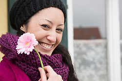 Portrait of a mid adult woman holding a pink gerbera daisy flower and smiling, Bavaria, Germany