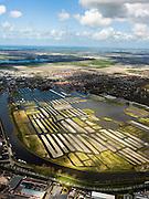 Nederland, Noord-Holland, Gemeente Langedijk, 16-04-2012; het Kanaal Alkmaar - Kolhorn scheidt bedrijventerrein Zandhorst (voorgrond) van landschapsreservaat Oosterdel. Dit gebied vormt een restant van het 'duizend eilandenrijk', voormalige veengronden ontstaan door ontwatering en afgraven van veen en in gebruik voor tuinbouw. Onderdeel van de Provinciale Ecologische Hoofdstructuur (EHS). Aan de horizon Broek op Langedijk.Landscape reserve Oosterdel (NW Netherlands) . This area is a remnant of thousand islands, former peatlands caused by drainage and excavation of peat and is used horticulturally. Part of the Provincial  Ecological Structure  (EHS).   .luchtfoto (toeslag), aerial photo (additional fee required);.copyright foto/photo Siebe Swart