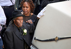 20 November 2015. Orpheum Theater, New Orleans, Louisiana. <br /> Memorial service for musician Allen Toussaint. Cyril Neville touches the hearse as people  spill out of the Orpheum Theater in a second line procession following the touching memorial service for one of the city's most influential musicians. <br /> Photo; Charlie Varley/varleypix.com