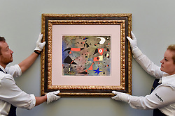 """© Licensed to London News Pictures. 15/06/2017. London, UK. Technicians hang """"Femme et oiseaux"""", 1940, by Joan Miró (estimate on request).  Preview of Impressionist and Modern art sale, which will take place at Sotheby's New Bond Street on 21 June.  Photo credit : Stephen Chung/LNP"""