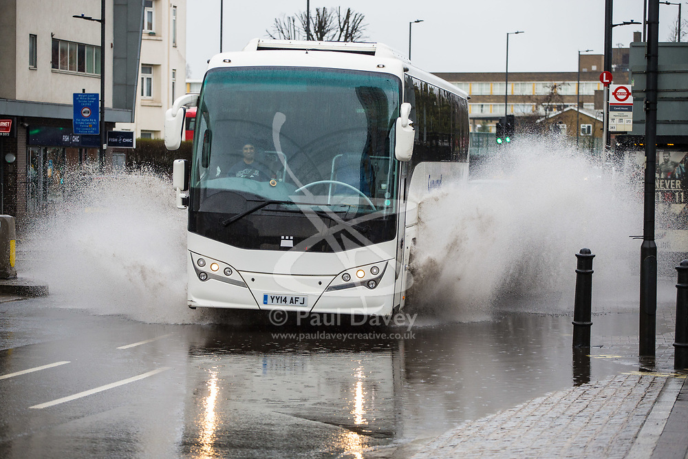 A bus driver grins as he drives his coach through a deep puddle after a night of heavy rain in London leaves part of Scrubbs Lane in Shepherd's Bush flooded. London, April 02 2018.