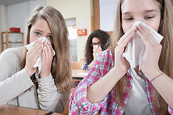 University students blowing nose with handkerchief, Bavaria, Germany