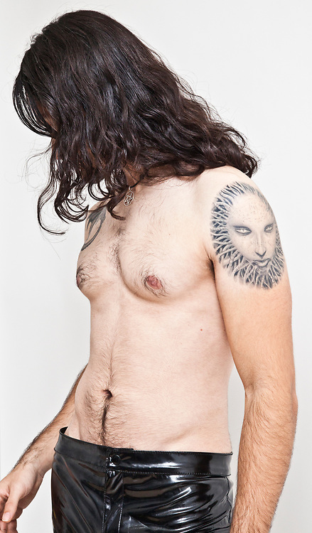 Young topless young man with tattoo on his shoulder